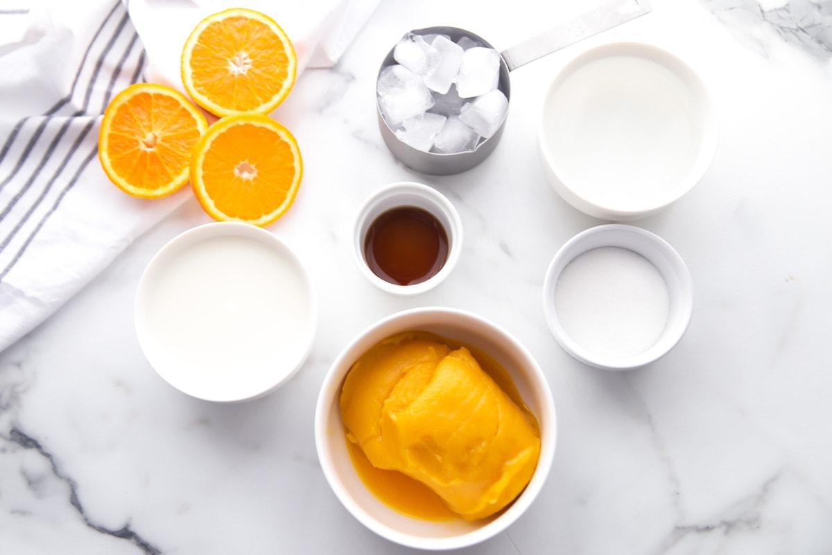 orange julius ingredients on a marble countertop