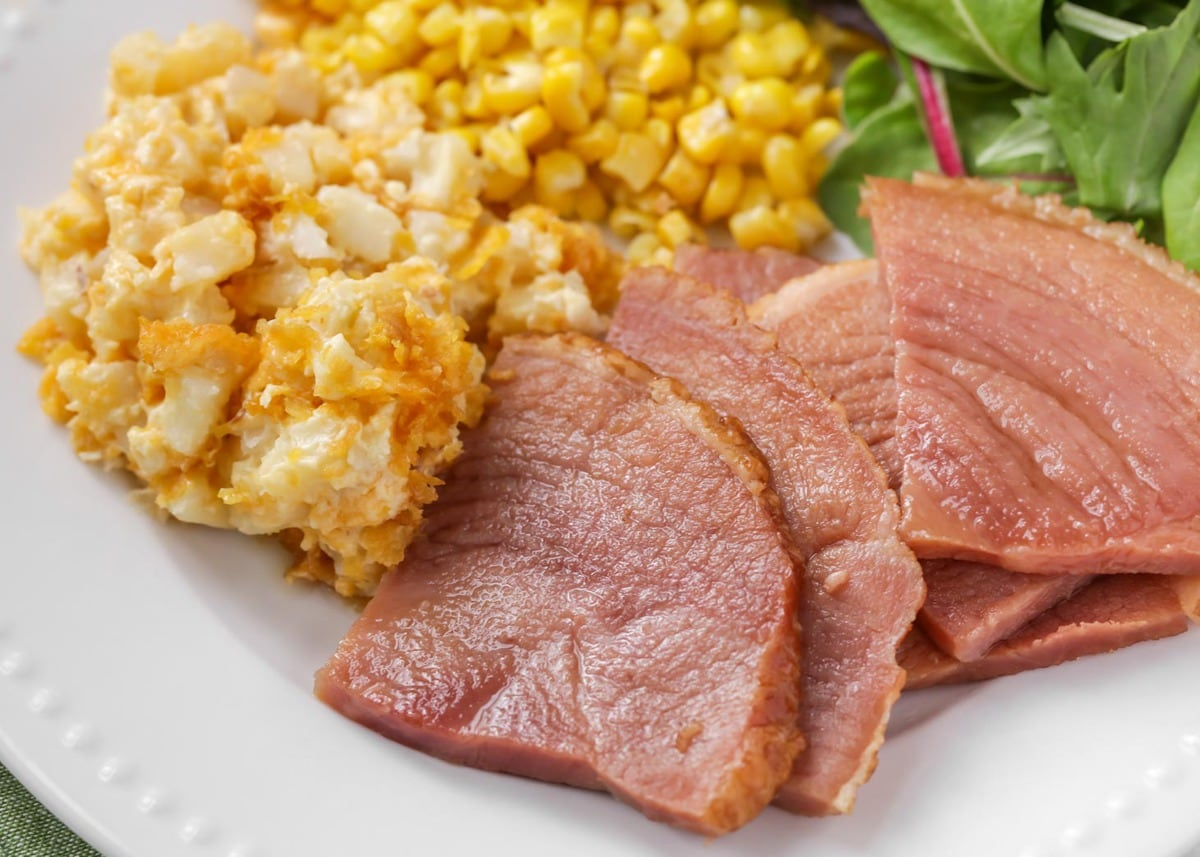 Crock Pot ham slices on plate with sides