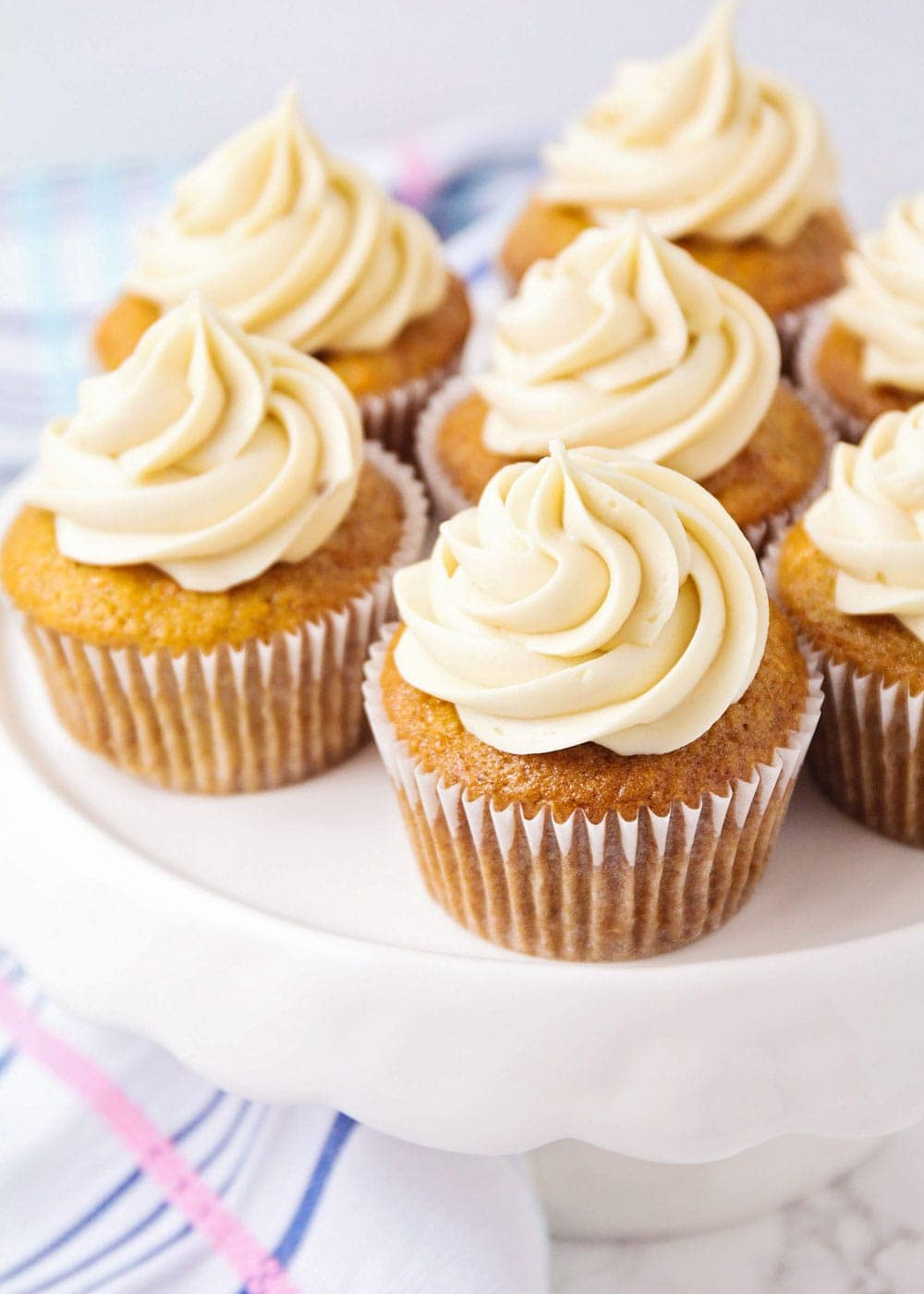 Carrot cake cupcakes recipe on white cake stand