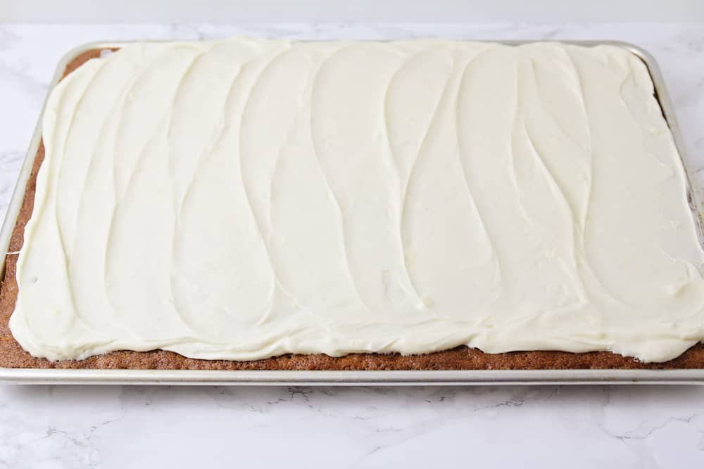 Cream cheese frosting spread onto carrot cake