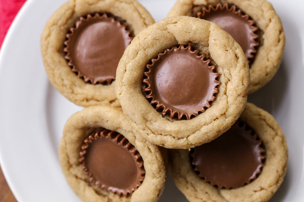 Five peanut butter cup cookies stacked on a white plate