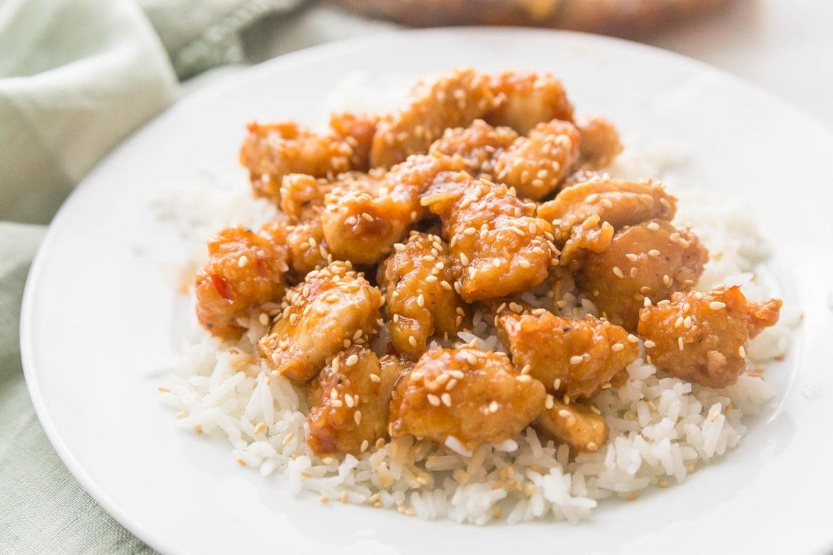 Sesame chicken on white plate close up