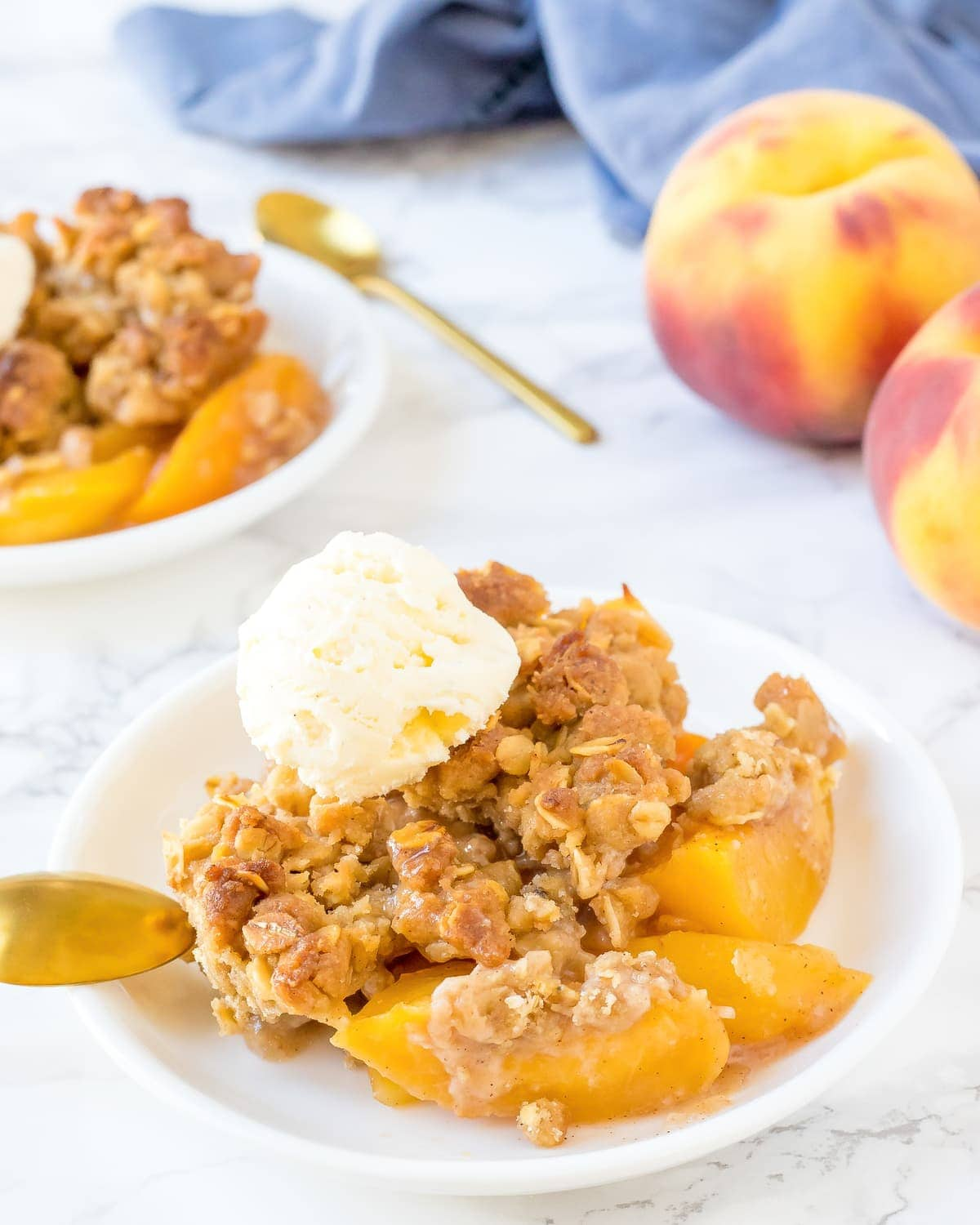 Easy peach crisp in bowl with ice cream