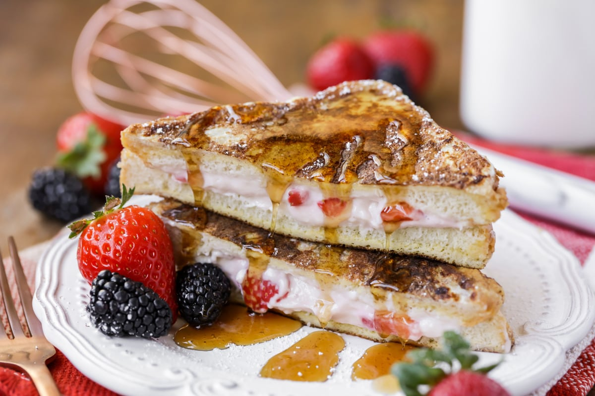 stuffed french toast topped with syrup and served with fresh berries