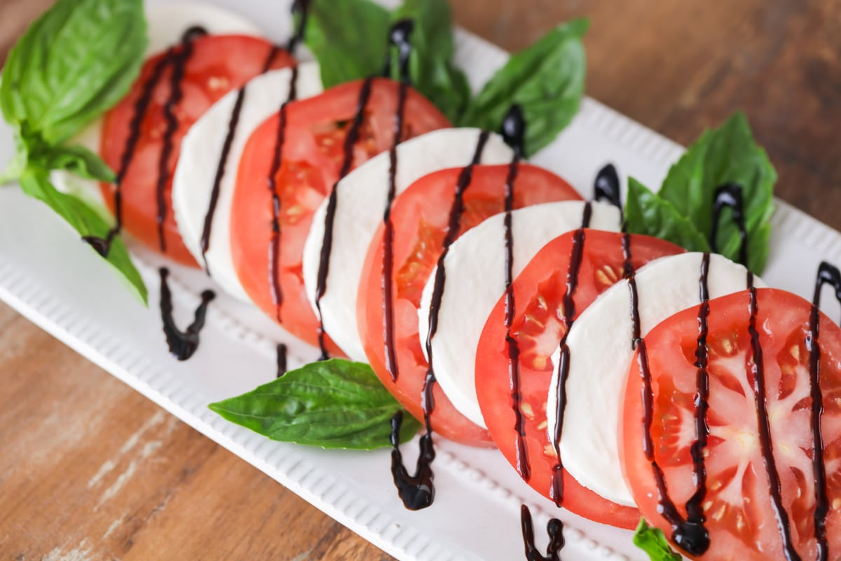 Tomato mozzarella salad on a platter with fresh basil and balsamic glaze