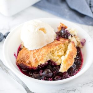 Delicious blueberry cobbler with a fluffy biscuit top and tons of juice blueberries served with a scoop of vanilla ice cream.