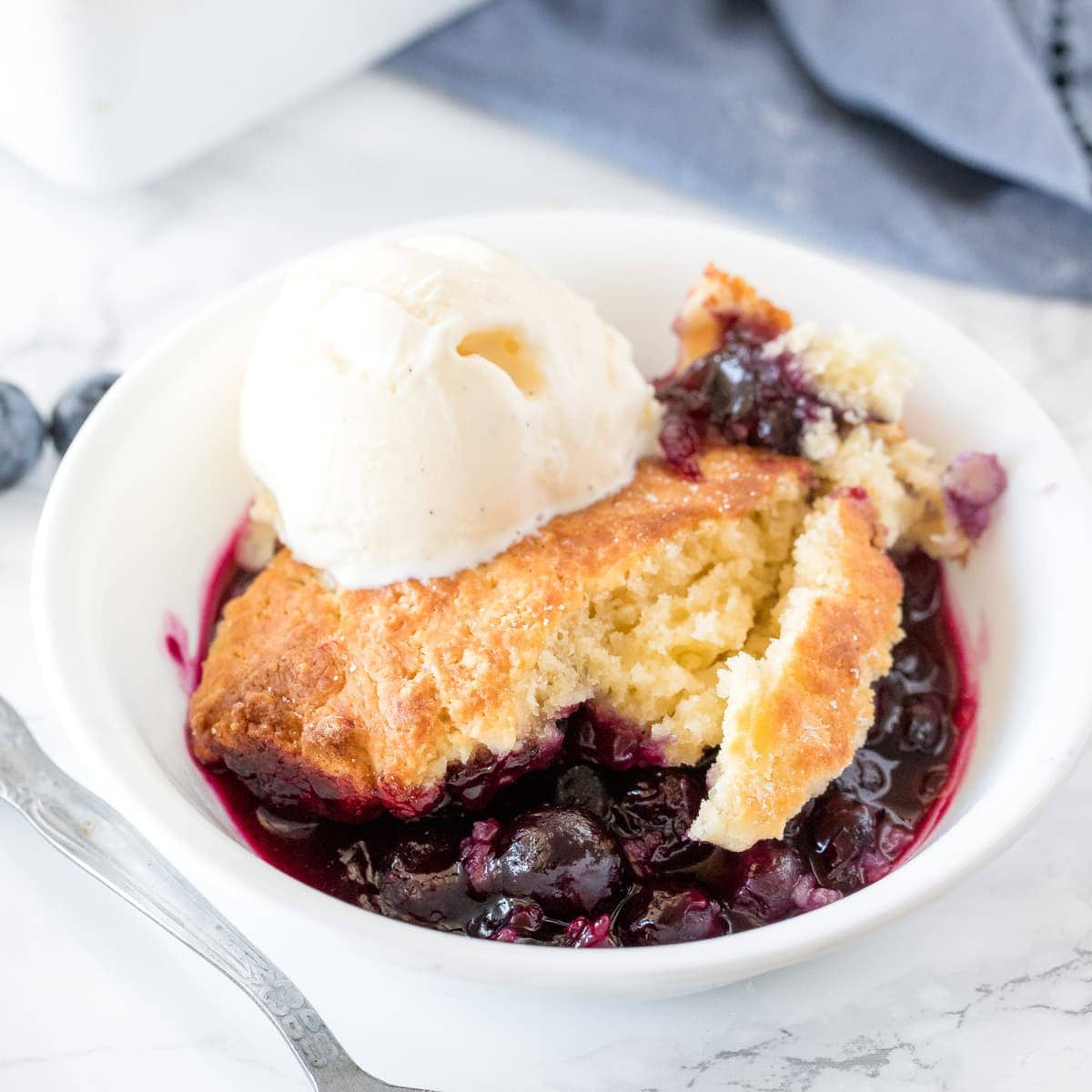 Scoop of blueberry cobbler with vanilla ice cream in a white bowl