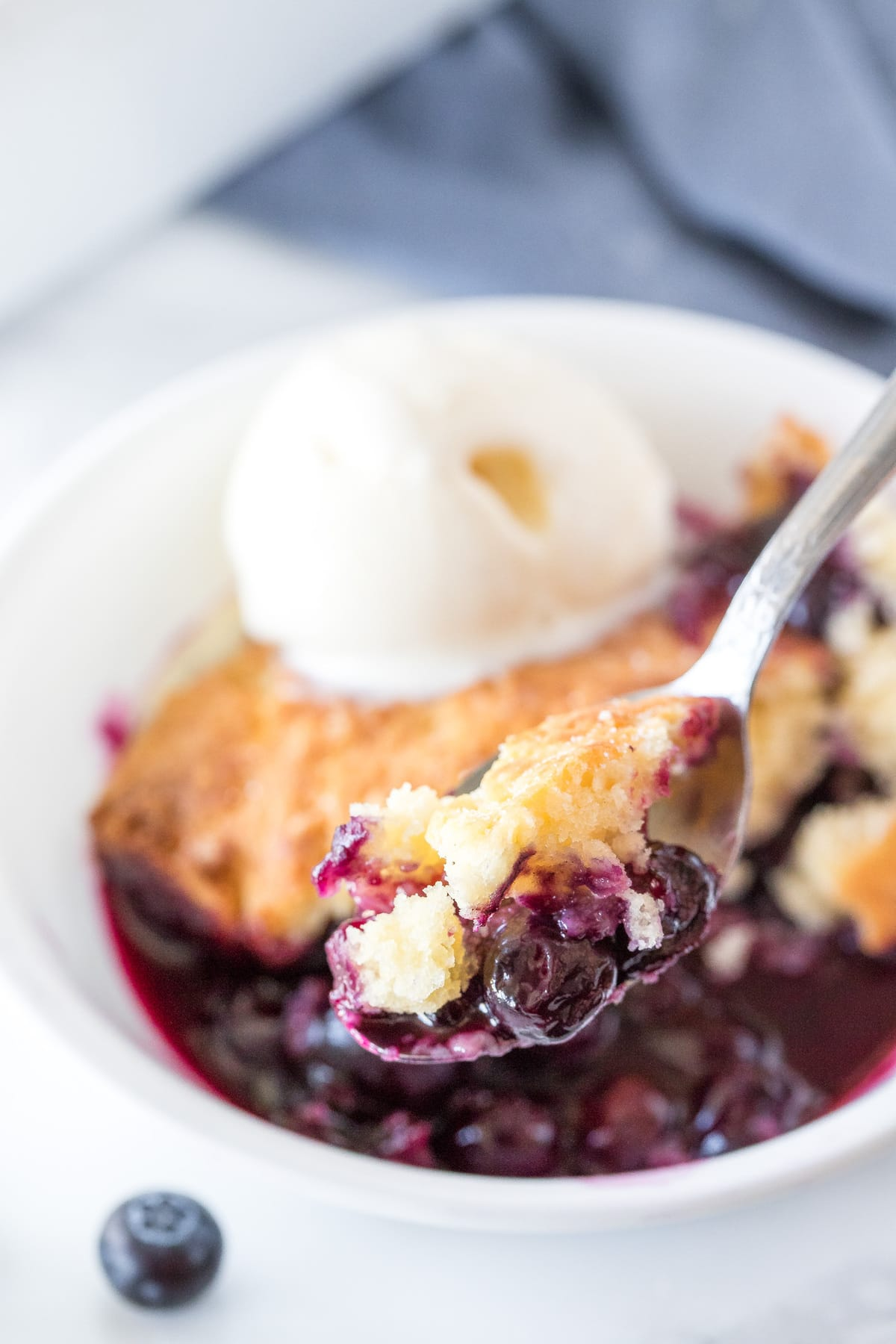 Fresh blueberry cobbler topped with ice cream in white bowl