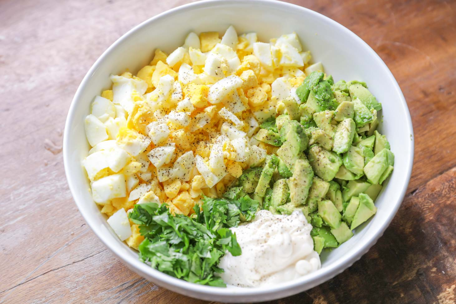 All ingredients for avocado egg salad in a white bowl