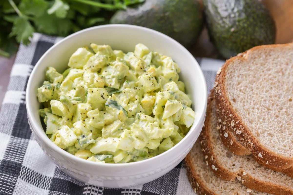 Avocado egg salad in a white bowl next to bread slices