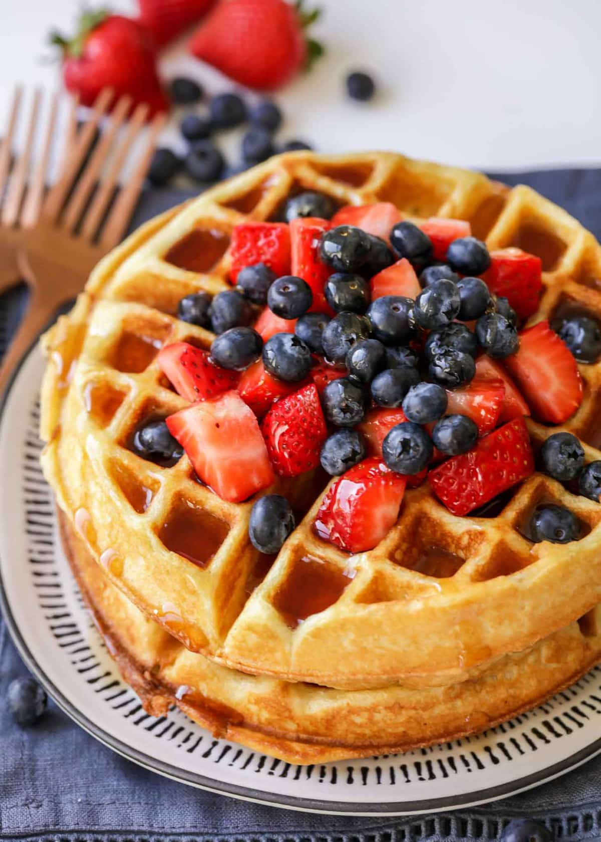 homemade buttermilk waffle topped with berries and syrup