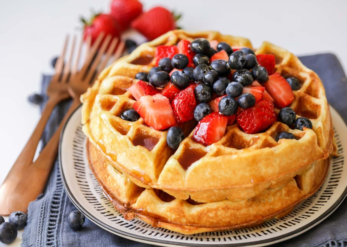 A stack of Buttermilk Waffles on a plate, topped with strawberries and blueberries