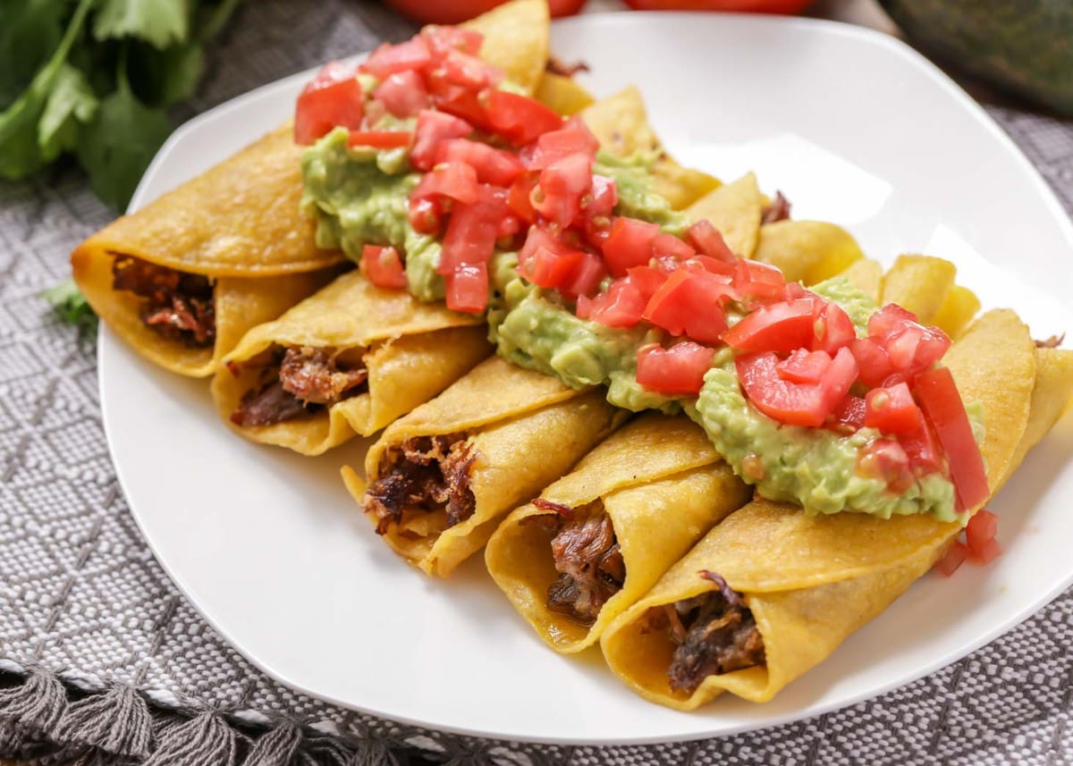 Beef flautas topped with guacamole and fresh tomatoes on a white plate