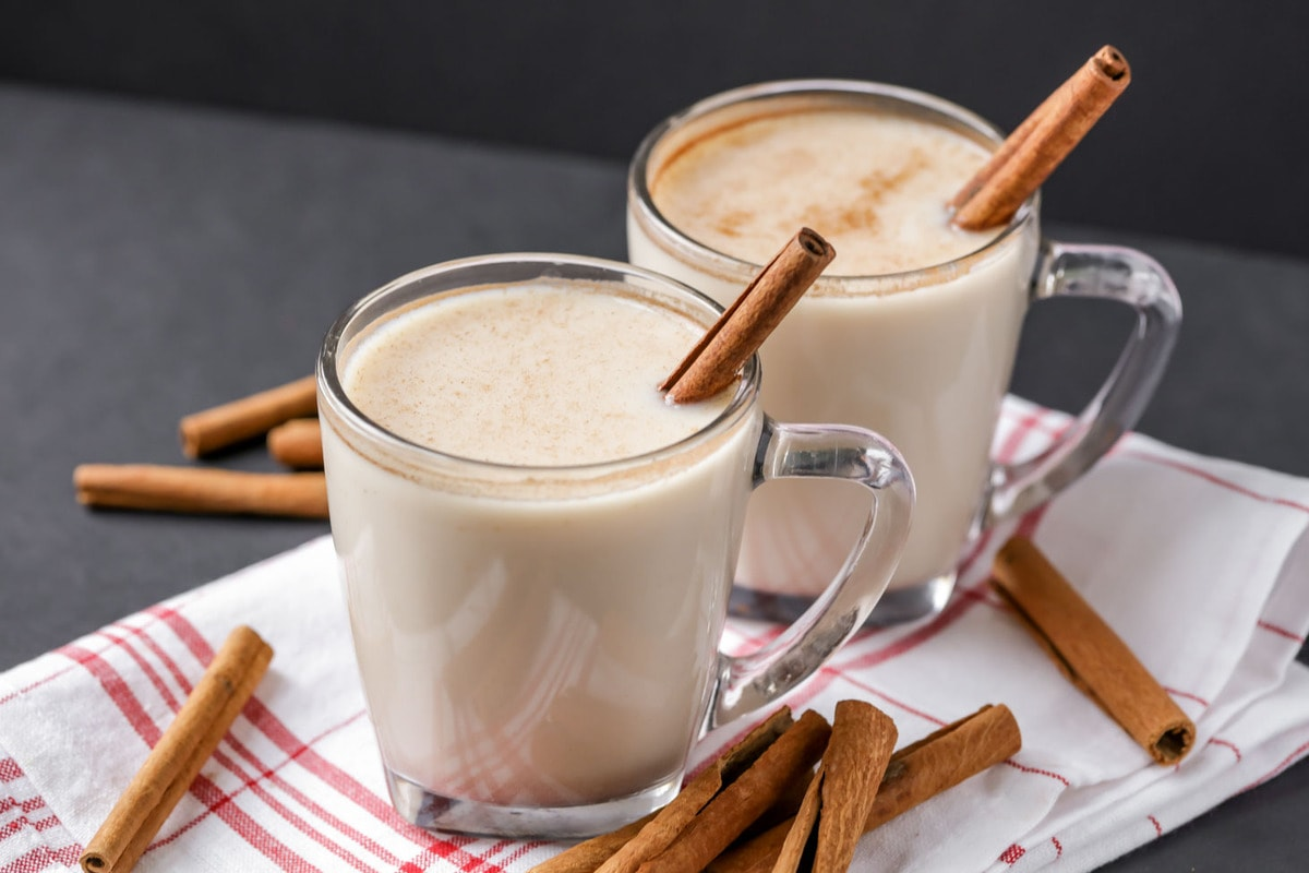 two glasses of horchata with cinnamon sticks as a garnish