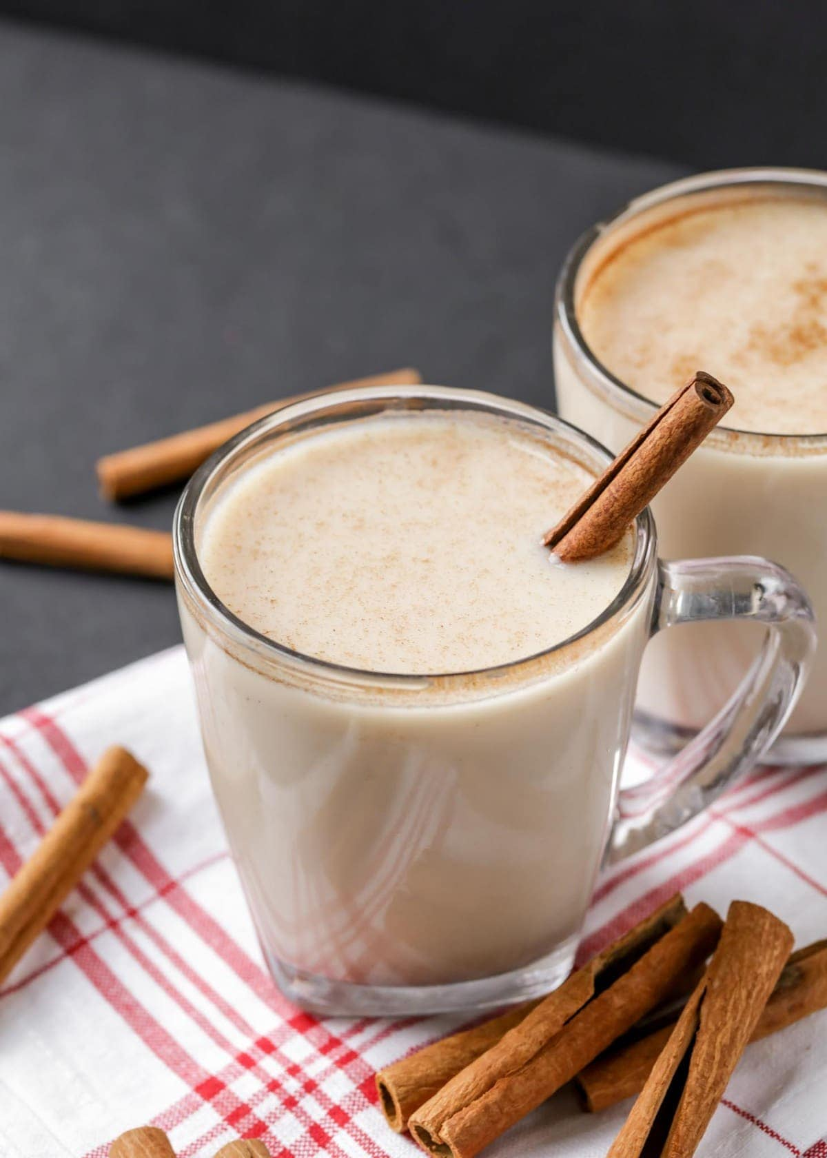 close up of horchata in a glass with a cinnamon stick for garnish