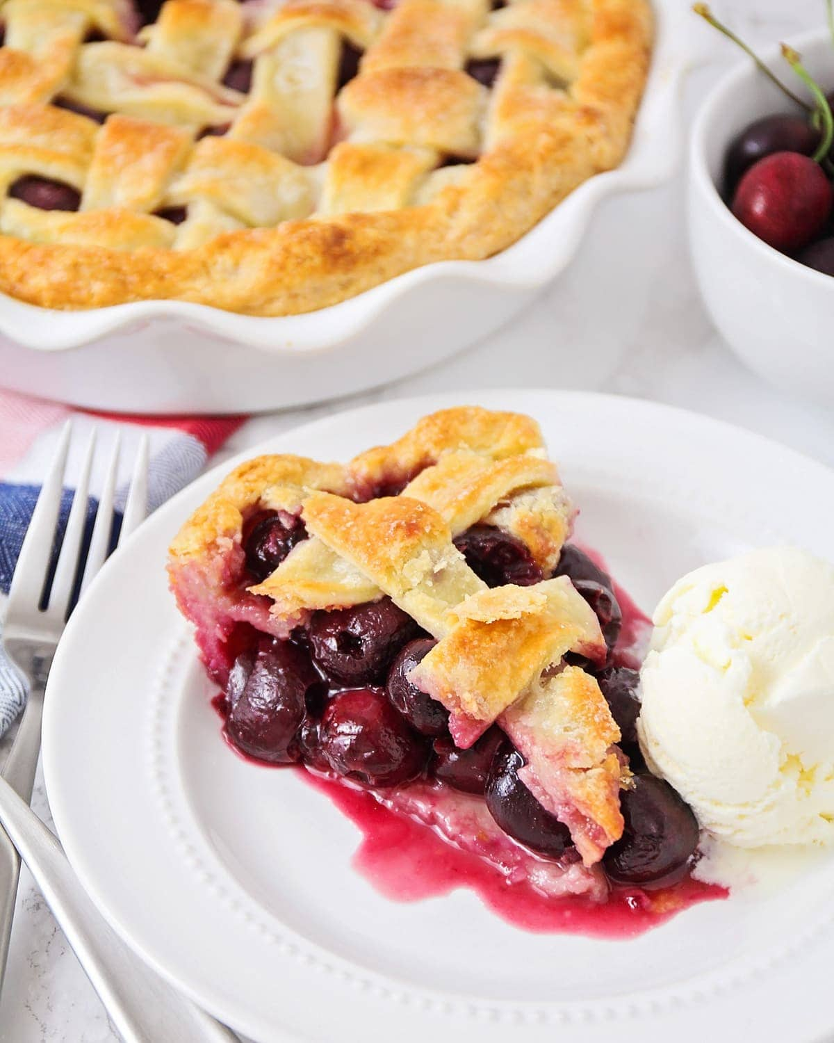Cherry pie slice on plate with ice cream