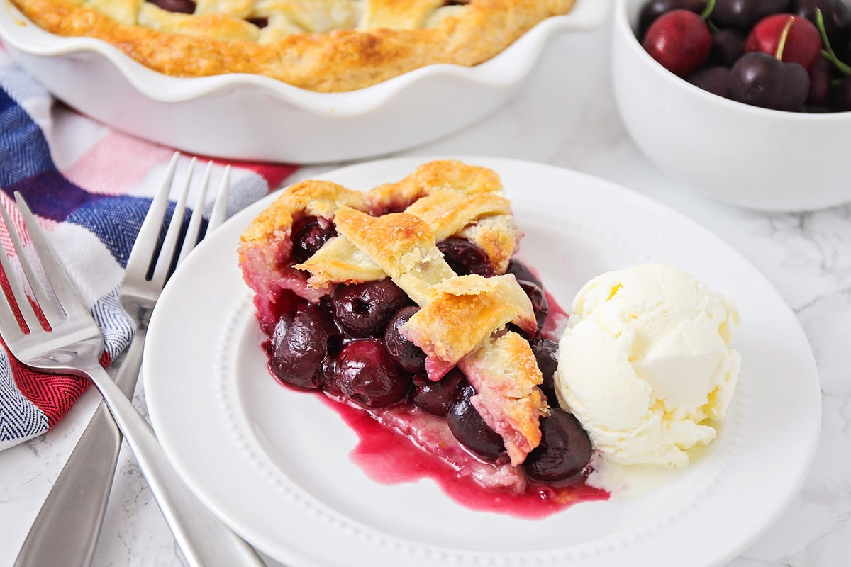 A slice of cherry pie with a scoop of vanilla ice cream on a plate