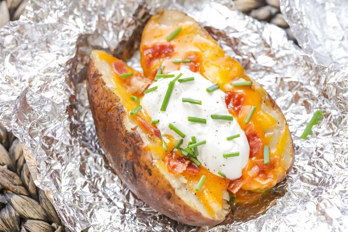 Crock pot baked potato topped with cheese, bacon, and sour cream
