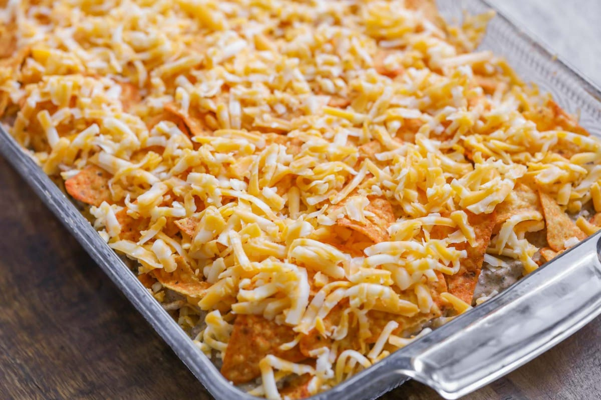 taco casserole with doritos and cheese layered on top