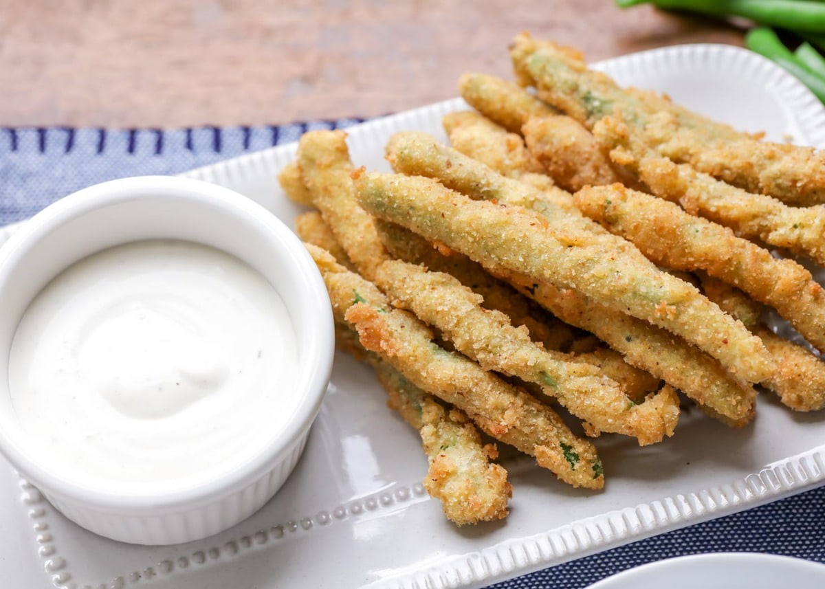 Green Bean fries on a platter with ranch dipping sauce