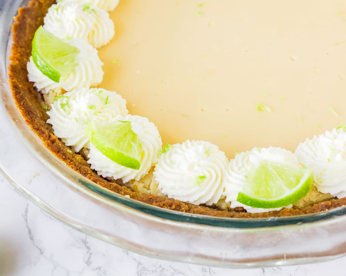 easy key lime pie topped with whipped cream and key limes