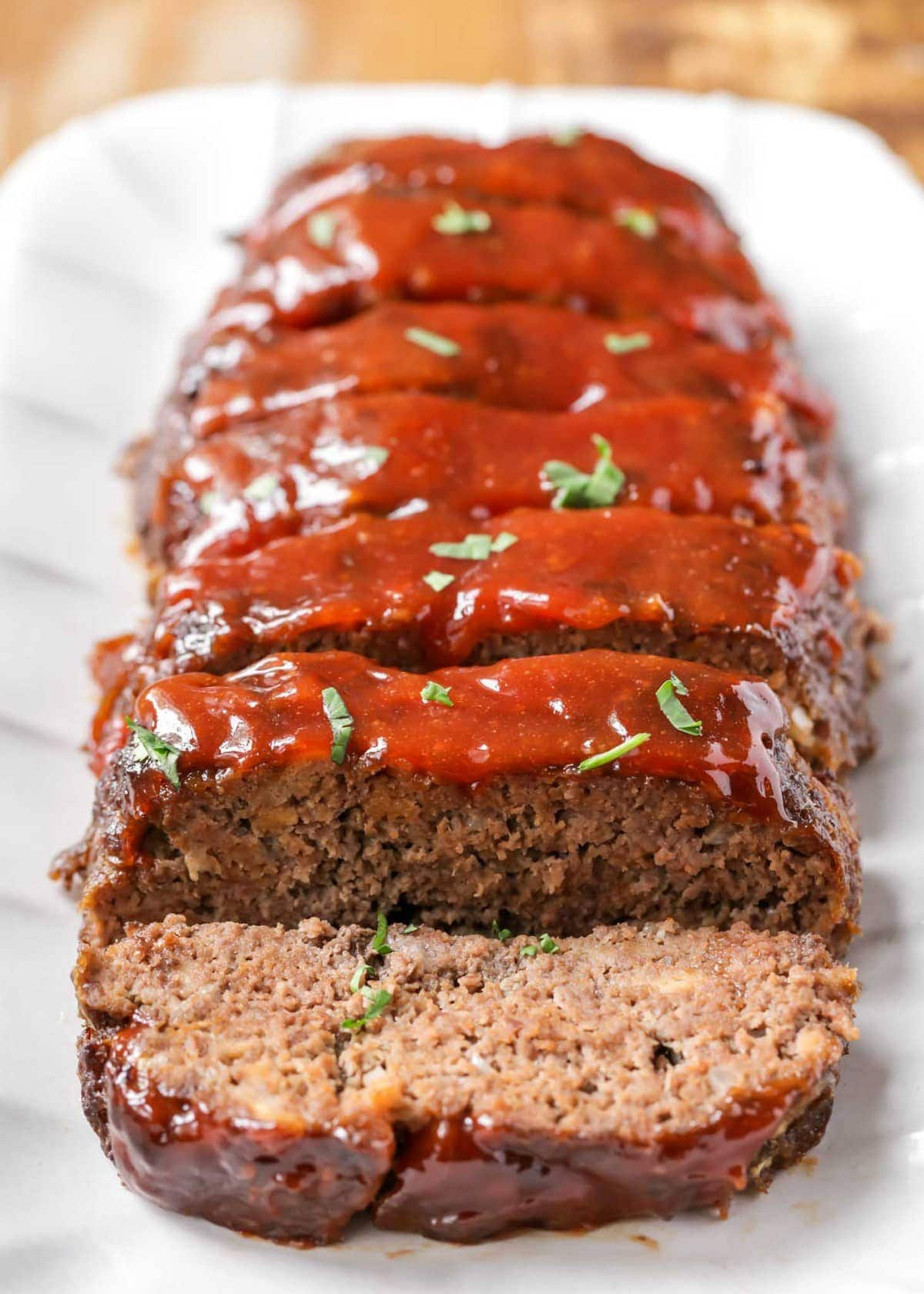 Homemade meatloaf cut into slices on a serving platter