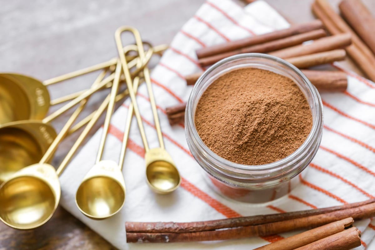 Pumpkin pie spice in a glass jar surrounded by cinnamon sticks