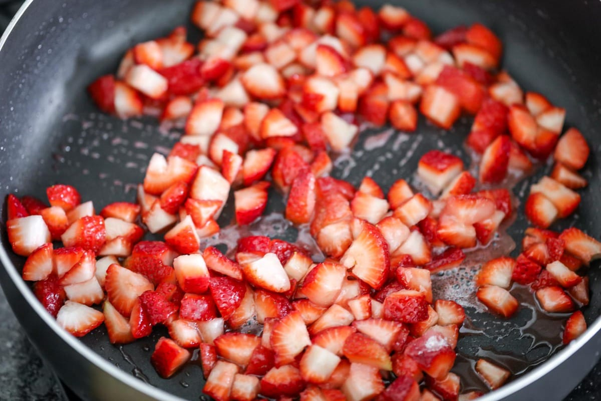 Fresh strawberries cooking in a skillet