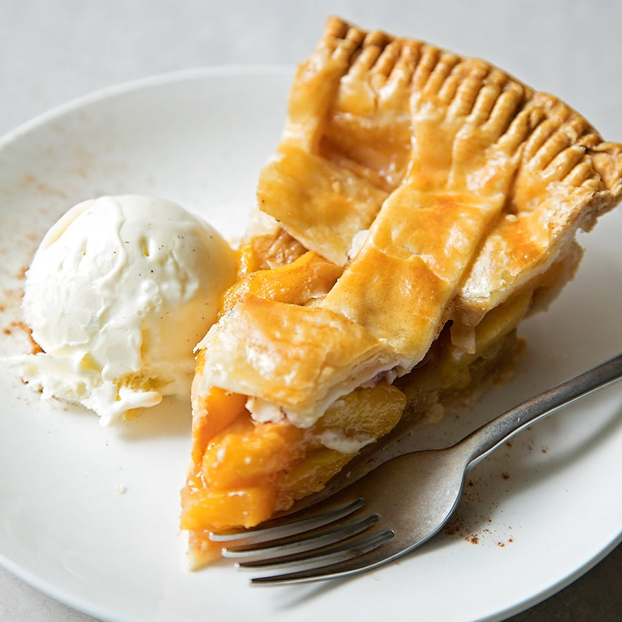 A slice of Peach Pie on a plate with a scoop of vanilla ice cream