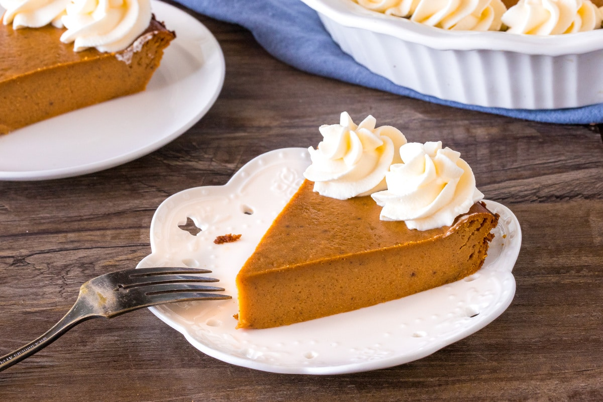 A slice of crustless pumpkin pie with whipped cream on top.