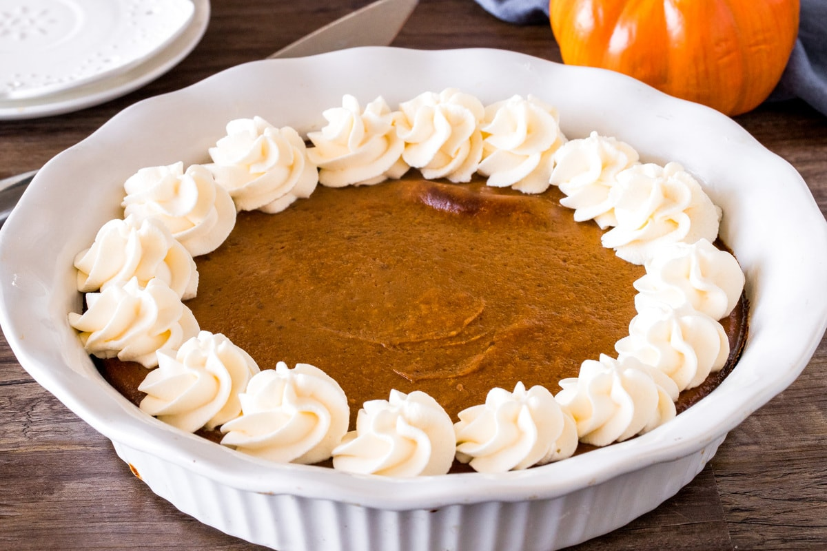 Crustless pumpkin pie with whipped cream around the edges
