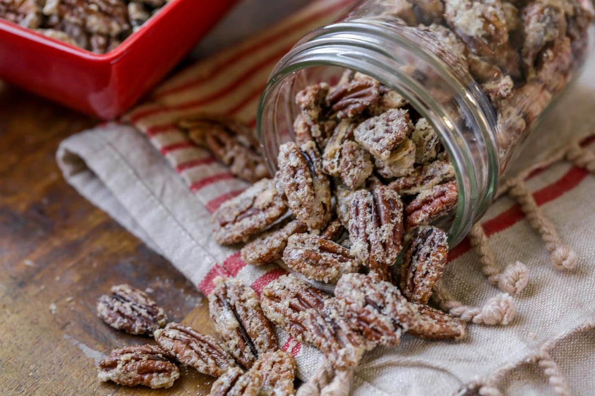 candied pecans spilling out of a glass jar