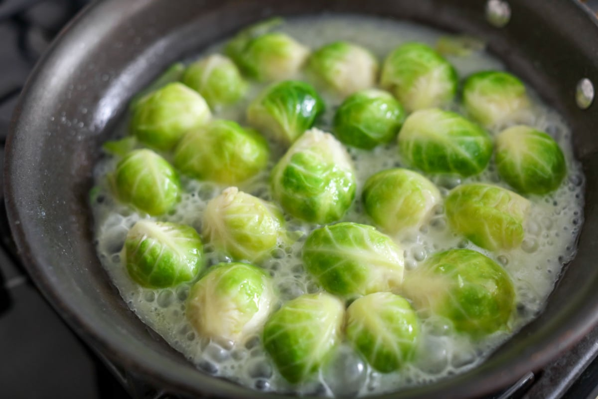 Glazed brussel sprouts being cooked in a skillet