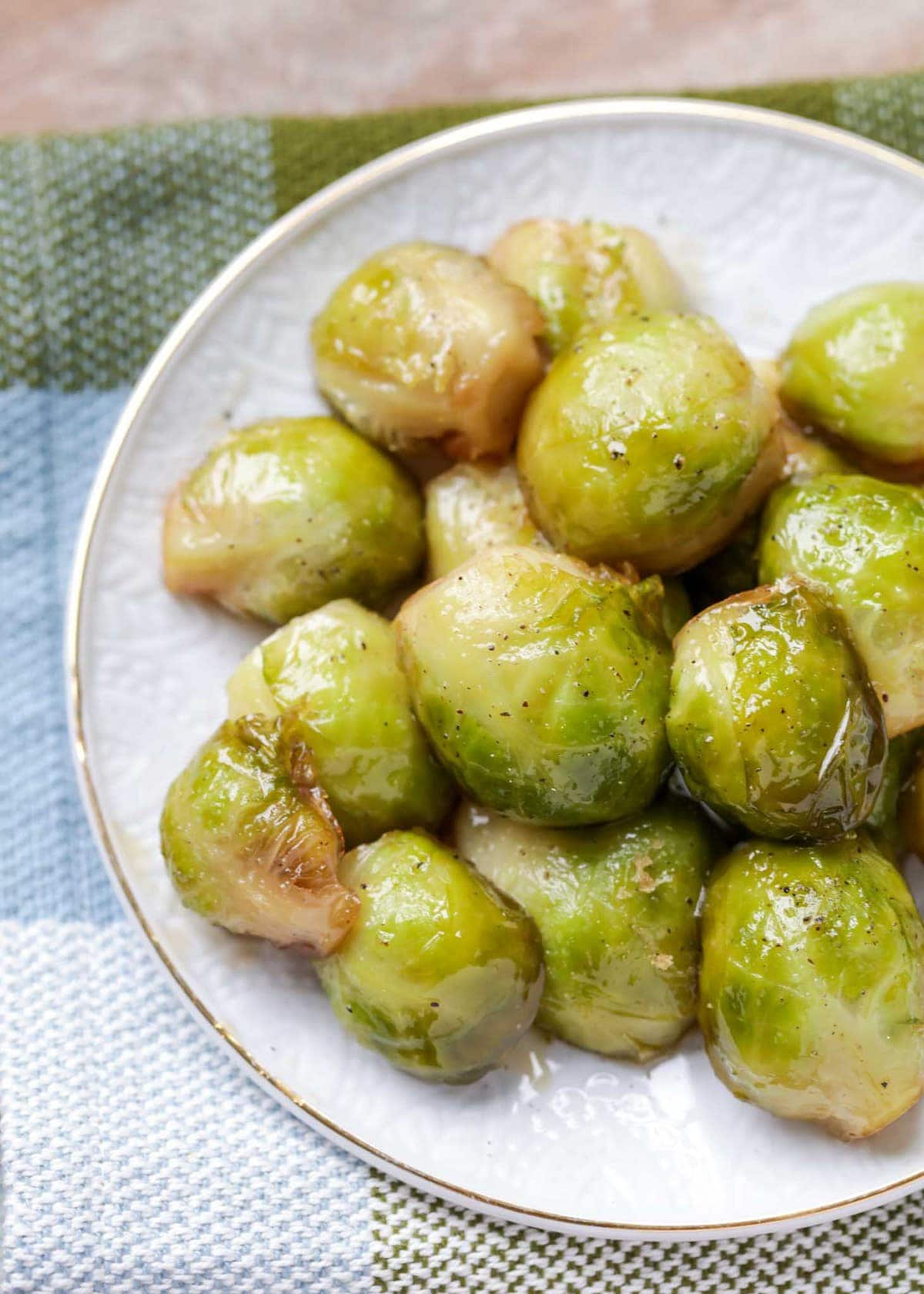 Close up of caramelized brussel sprouts on a white plate