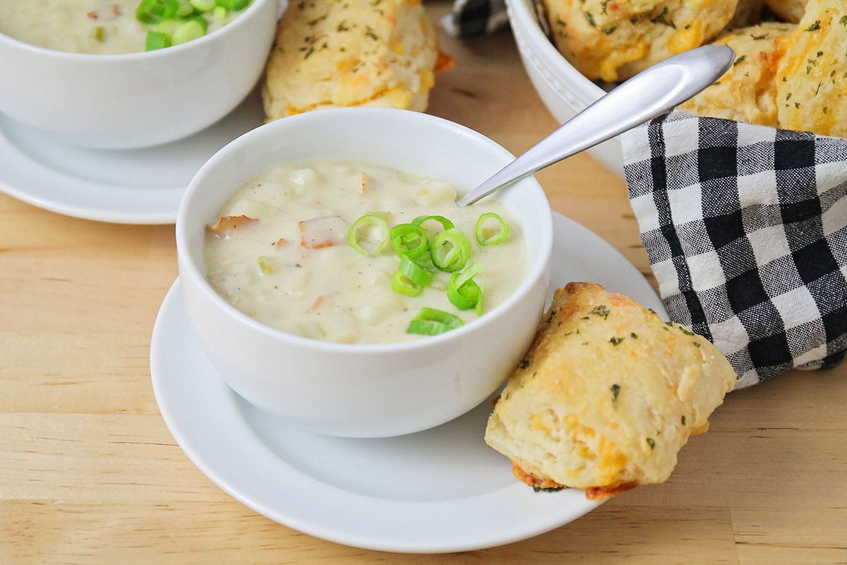 clam chowder in a white bowl with biscuits on the side