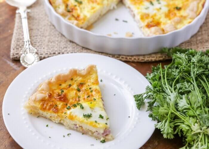 A slice of ham and cheese quiche on a white plate