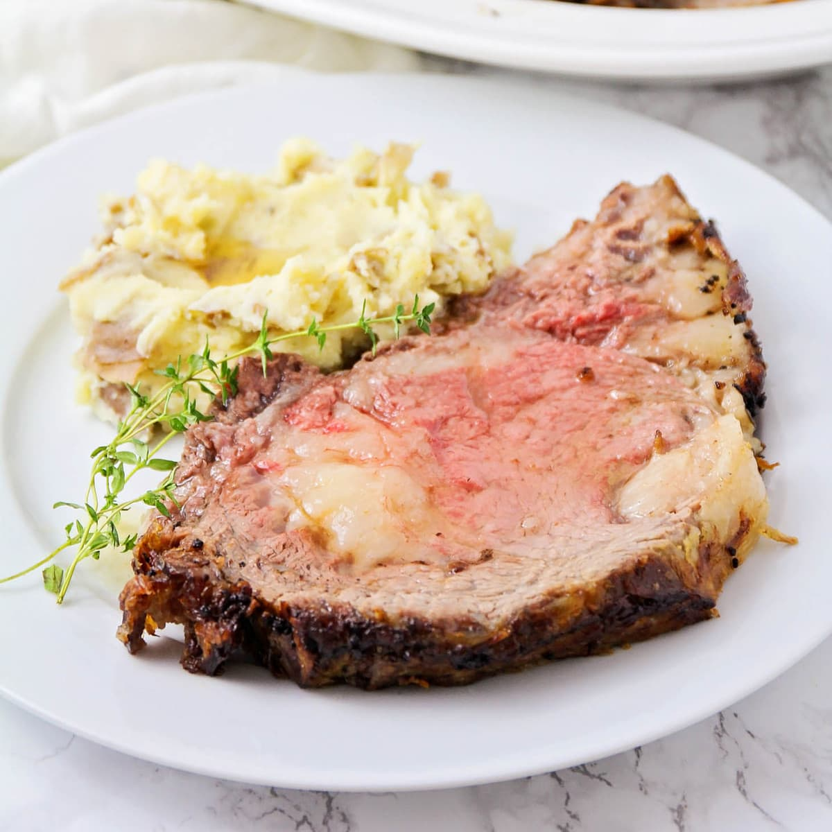 A slice of perfect prime rib on a plate with a side of potatoes