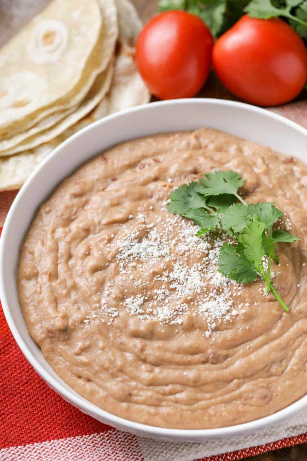 Restaurant style refried beans in a white bowl topped with cilantro