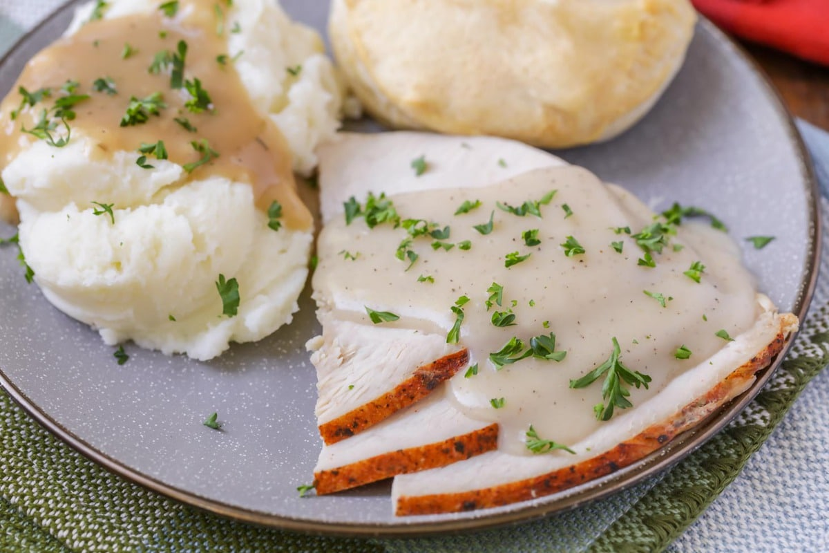turkey gravy over slices of turkey and mashed potatoes