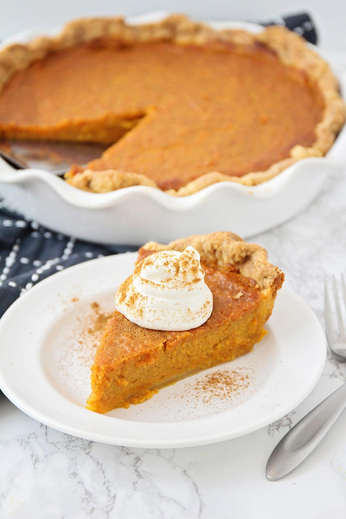 slice of homemade sweet potato pie with a dollop of whipped cream