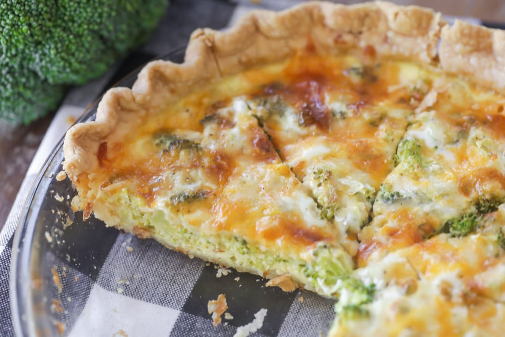 broccoli cheese quiche in a pie dish with slices missing
