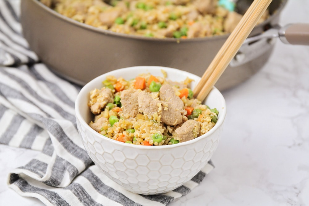 cauliflower fried rice in a bowl with chopsticks