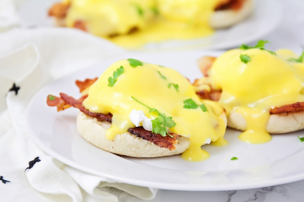 Eggs Benedict topped with fresh parsley on a white plate
