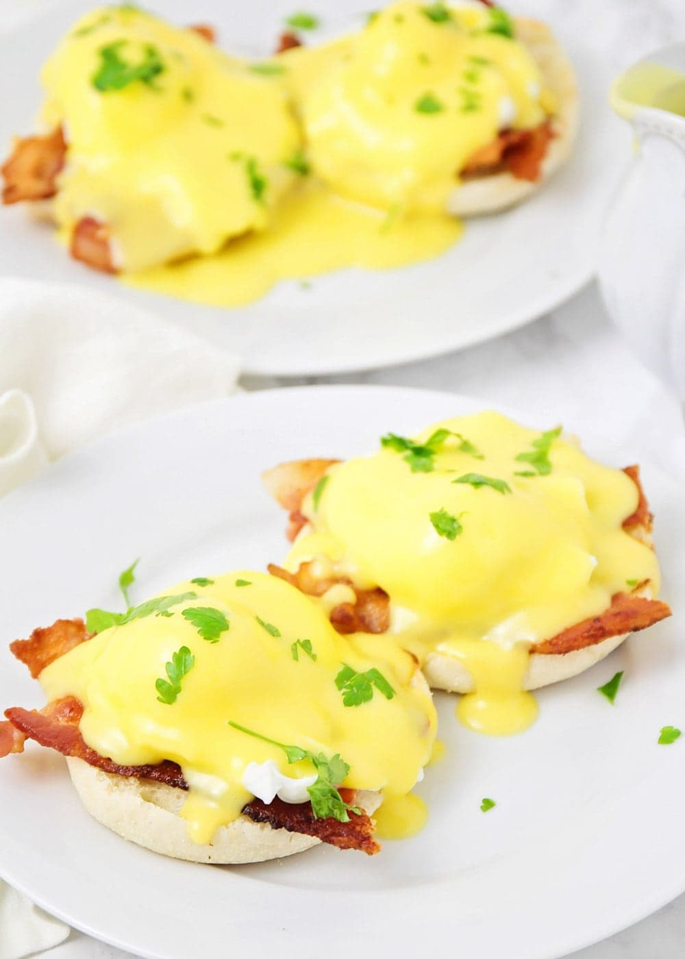 Close up of eggs Benedict smothered in homemade hollandaise sauce