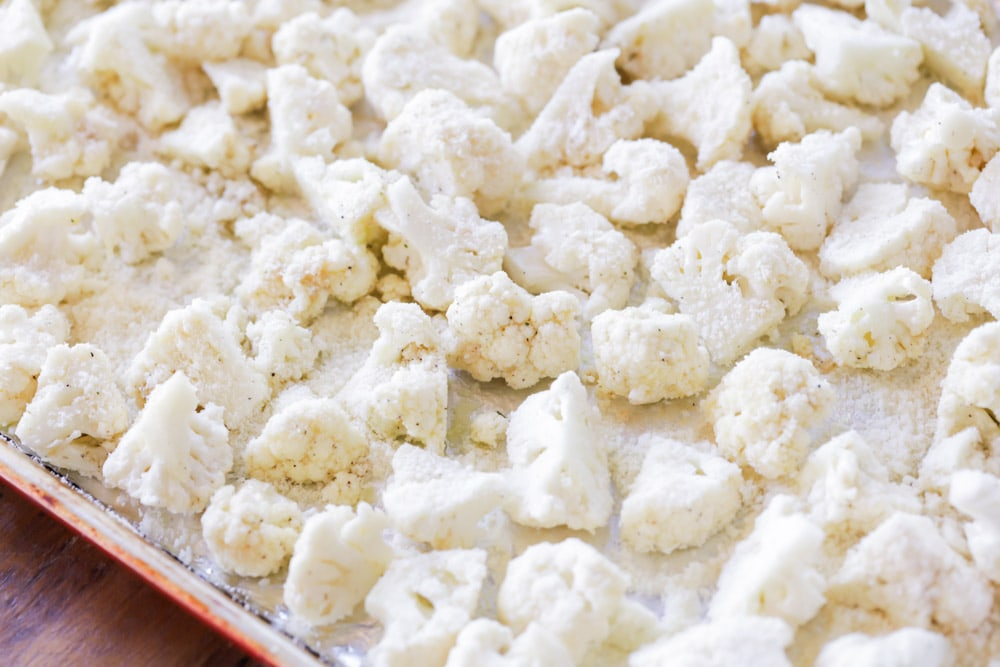 cauliflower covered in parmesan on a baking sheet