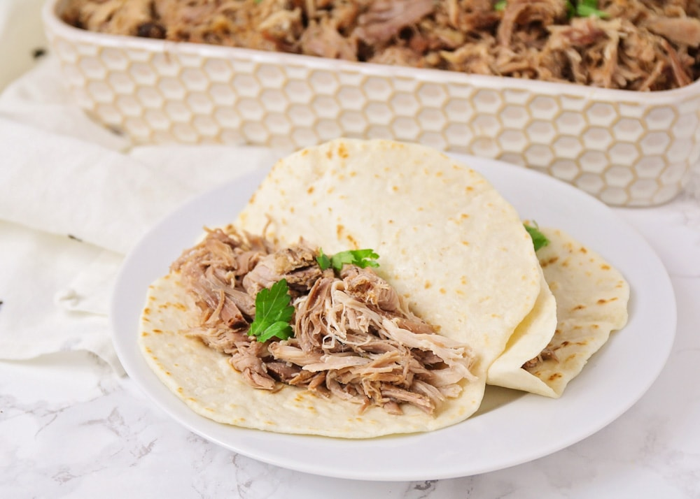 Two carnitas tacos on a white plate