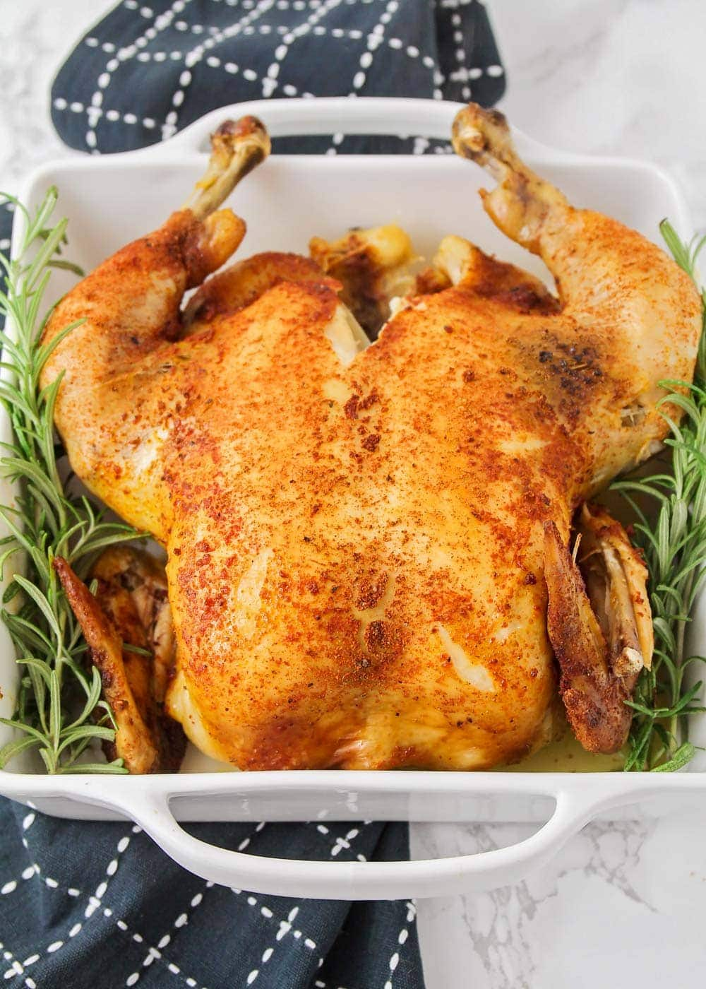 Slow cooker roast chicken in a serving dish with garnish
