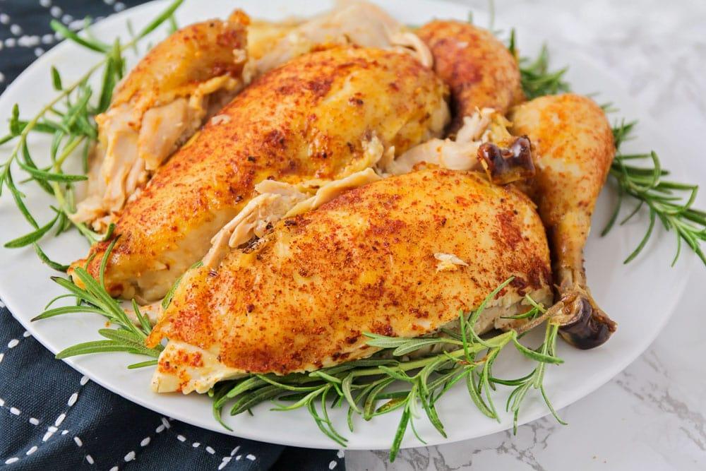 Crockpot roast chicken on a white platter with rosemary garnish