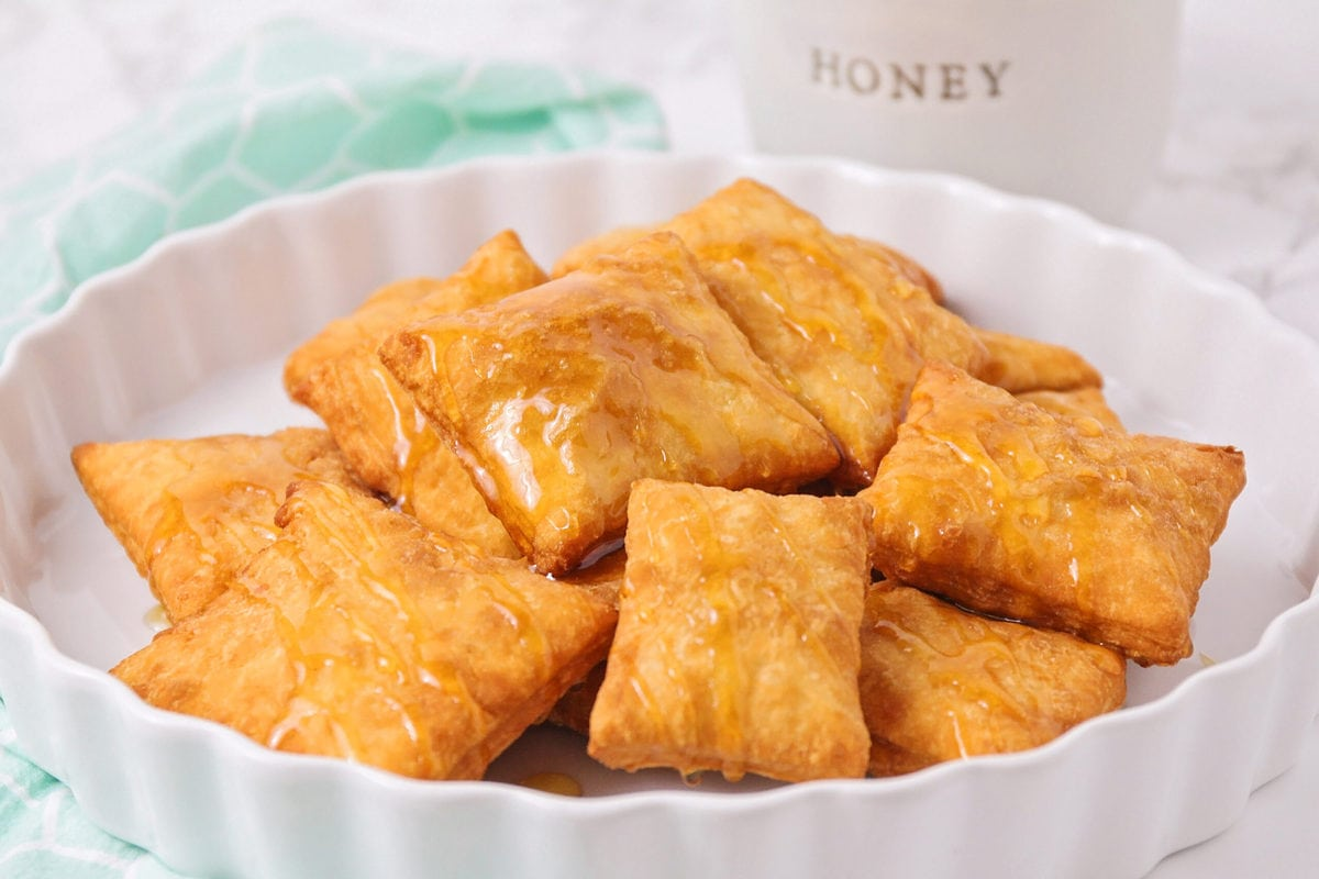 A pile of sopapillas on a white serving dish