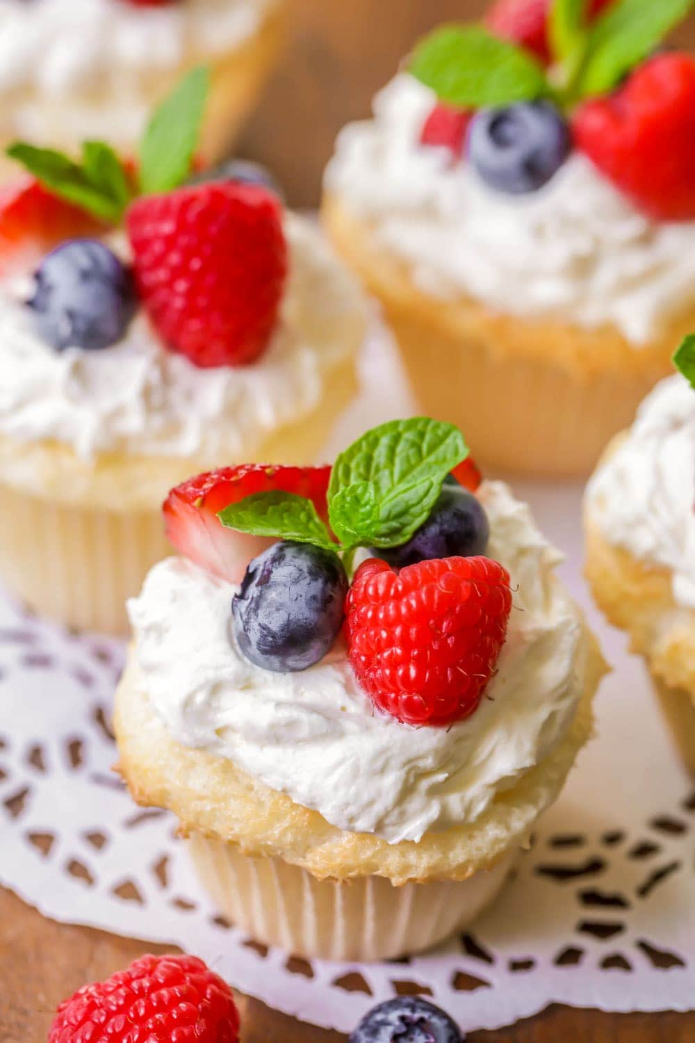 Close up of angel food cake cupcakes topped with frosting and berries